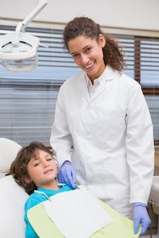Dentista pediátrica sorrindo com o menino na cadeira
