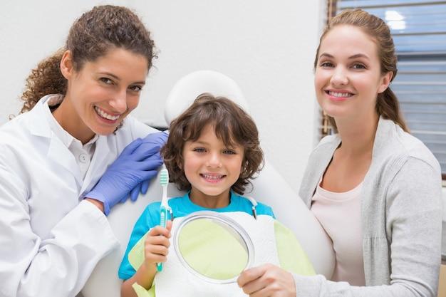 Dentista pediátrico que mostra o menino como escovar os dentes com sua mãe