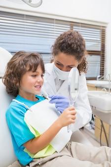 Dentista pediátrico que mostra o menino seus dentes no espelho