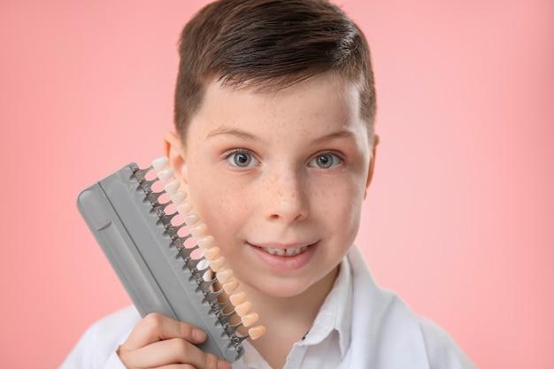 Dentista pequeno com amostras de cores de dentes em rosa