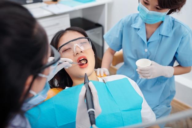 Dentista perfurando os dentes de uma jovem paciente com dor de dente