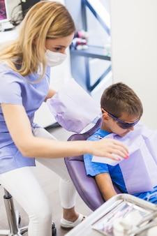 Dentista, preparando o menino para check-up odontológico