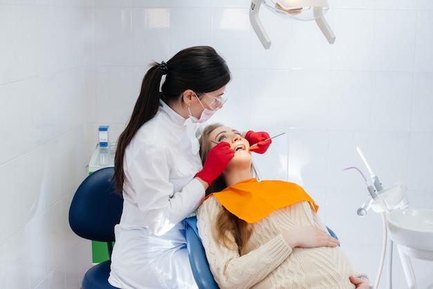 Dentista profissional trata e examina a cavidade oral de uma menina grávida em um consultório odontológico moderno. odontologia