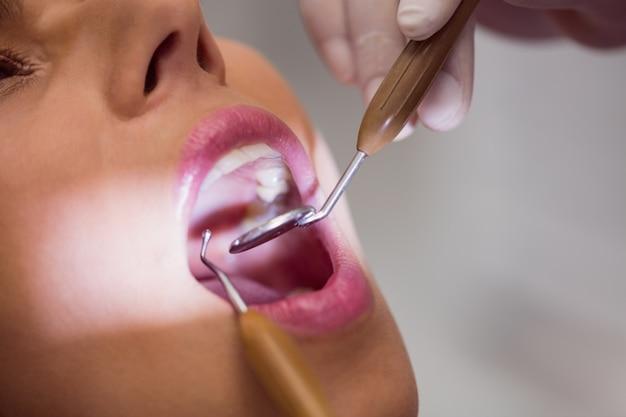 Dentista que examina os dentes pacientes do sexo feminino