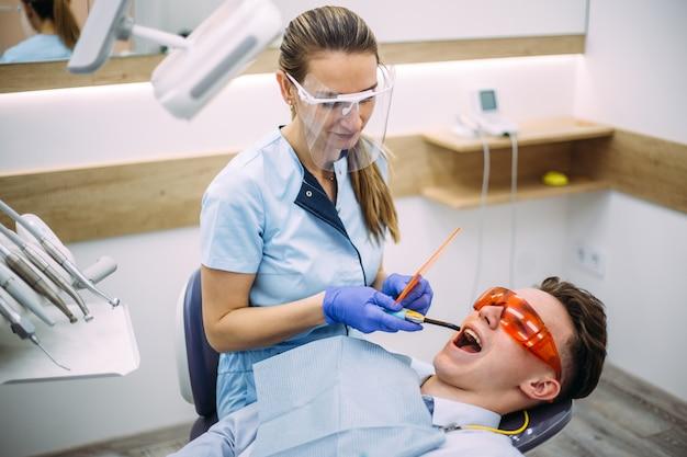 Dentista que trata um paciente com a ferramenta ultravioleta de cura dental.