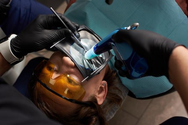 Dentista realiza tratamento odontológico a um paciente em óculos odontológicos laranja com uma borracha