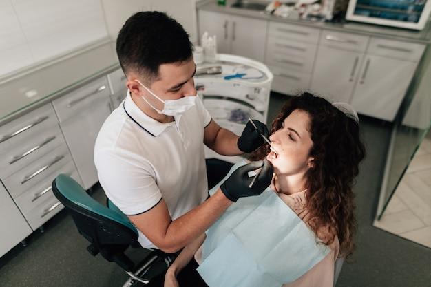 Dentista, realizando um check-up do paciente no escritório