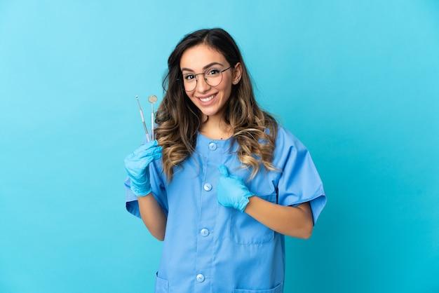 Dentista segurando ferramentas em azul com expressão facial surpresa