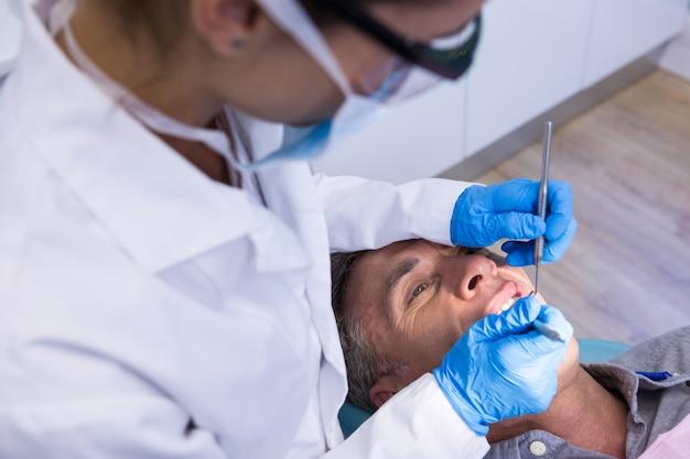 Dentista segurando ferramentas enquanto examina um homem na clínica