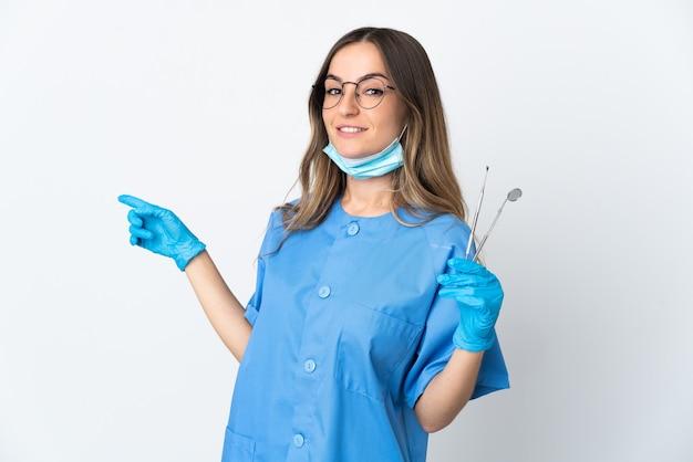Dentista segurando ferramentas isoladas, apontando o dedo para o lado