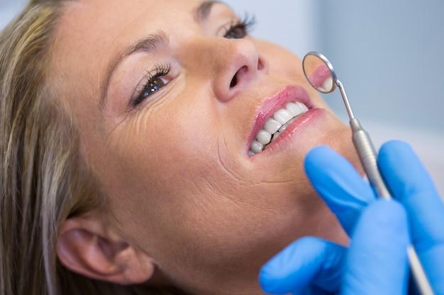 Dentista segurando um espelho angulado por uma mulher na clínica médica