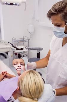 Dentista segurando um espelho perto do rosto de pacientes