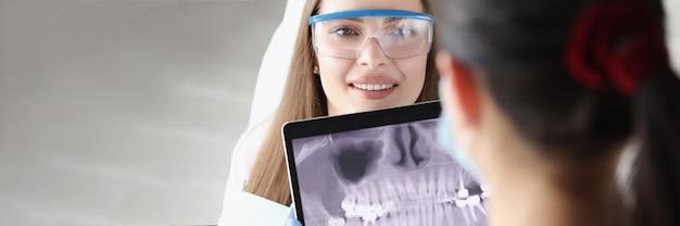 Dentista segurando um tablet digital com uma foto panorâmica da mandíbula na frente de uma paciente na clínica