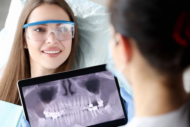 Dentista segurando um tablet digital com uma imagem de dentes nas mãos na frente de uma paciente