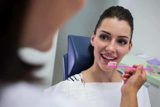 Dentista segurando uma escova na frente do paciente