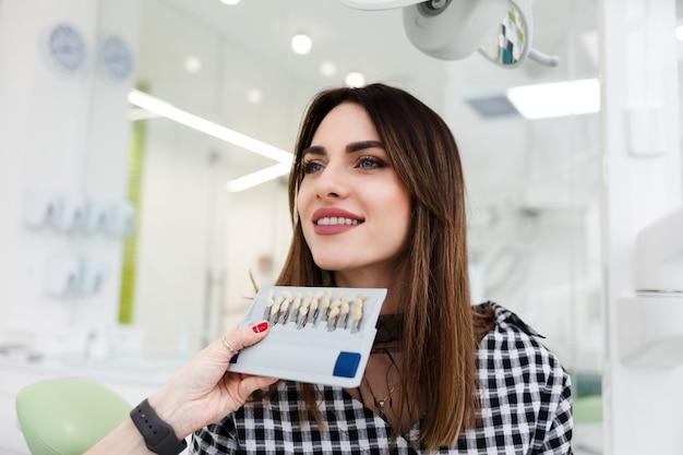 Dentista seleciona um tom de dentes para o paciente. conceito de atendimento odontológico profissional
