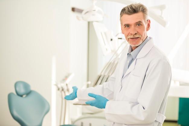 Dentista sênior de sorriso na clínica odontológica.