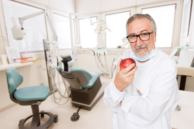 Dentista sênior no escritório com uma maçã