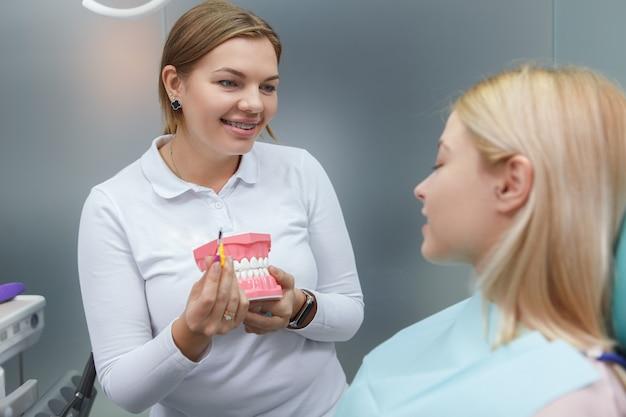 Dentista simpática com aparelho ortodôntico ensinando ao paciente a maneira correta de escovar os dentes, segurando modelo dental