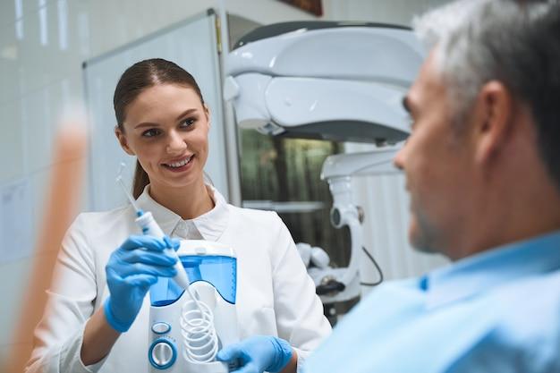 Dentista sorridente está demonstrando equipamentos modernos para dentes durante a consulta com o homem