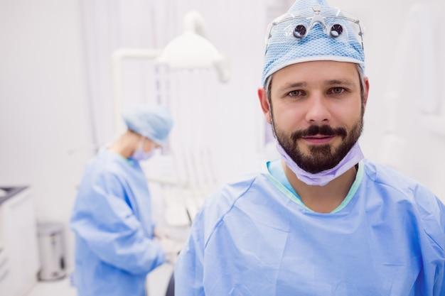 Dentista, sorrindo e posando na clínica odontológica