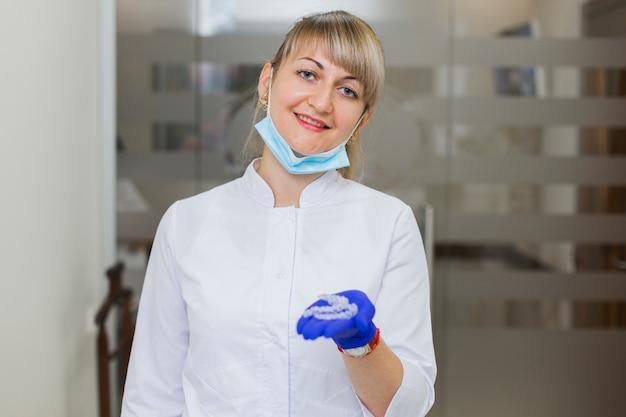 Dentista, sorrindo e segurando retentores invisíveis
