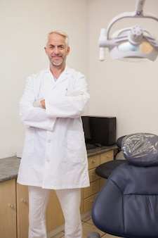 Dentista sorrindo para a câmera ao lado da cadeira