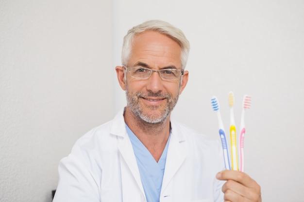 Dentista sorrindo para a câmera segurando escovas de dentes