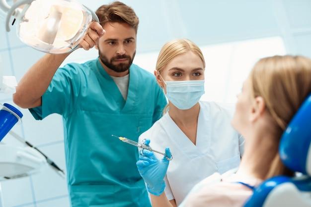Dentista tem instrumentos dentários nas mãos.