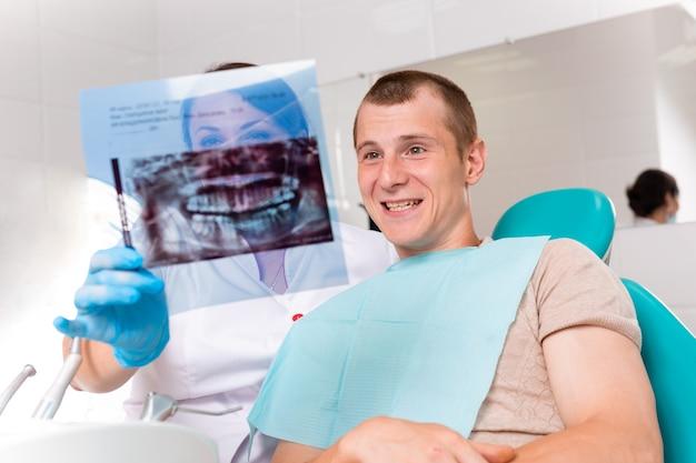 Dentista, terminando a restauração de dentes bem-sucedida, médico de cabelos pretos, na máscara verde