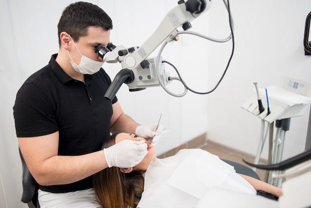 Dentista tratando dentes de pacientes em consultório odontológico