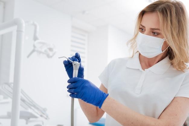 Dentista treinado e competente, mantendo e limpando o equipamento profissional que ela utiliza durante o tratamento de seus pacientes