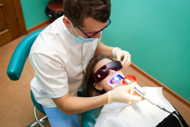 Dentista, usando a lâmpada ultravioleta de clareamento nos dentes. paciente jovem na clínica odontológica encontra-se em óculos uv na cadeira do dentista