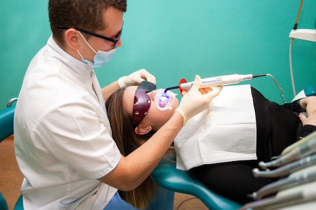 Dentista, usando a lâmpada ultravioleta de clareamento nos dentes. paciente jovem na clínica odontológica encontra-se em óculos uv