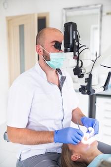 Dentista, usando, microscópio dental, para, tratamento, femininas, paciente, dentes