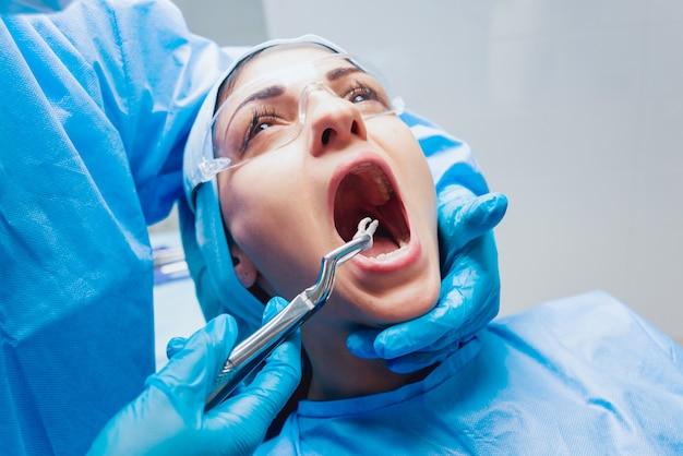 Dentista usando um alicate cirúrgico para remover um dente em decomposição. clínica odontológica moderna