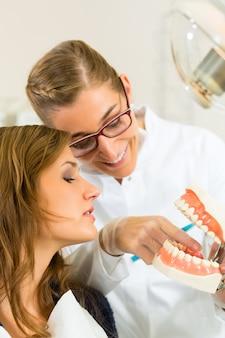 Dentistaesta cirurgia detém uma prótese e explica uma paciente do sexo feminino com uma escova de dentes