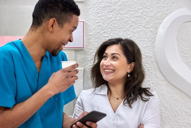 Dentistas africanos e caucasianos em coffee break