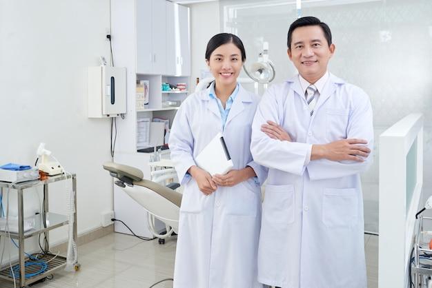Dentistas asiáticos alegres posando na sala de tratamento na clínica em frente ao equipamento