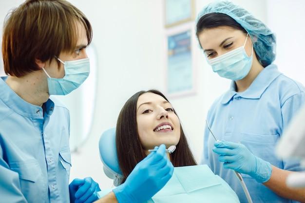 Dentistas com máscaras em um exame dentário