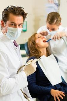 Dentistas, esta cirurgia realiza uma broca e, olhando para o espectador, o assistente dele está dando tratamento a uma paciente do sexo feminino
