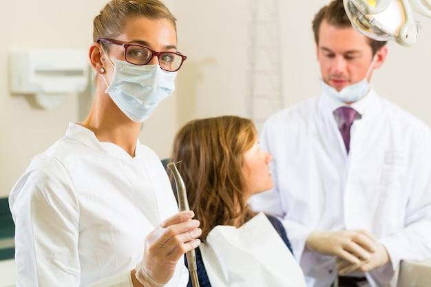 Dentistas, esta cirurgia realiza uma broca e, olhando para o espectador, o colega está dando tratamento a uma paciente do sexo feminino