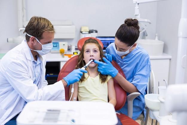 Dentistas examinando um jovem paciente com ferramentas