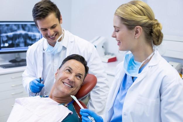 Dentistas interagindo com um paciente do sexo masculino