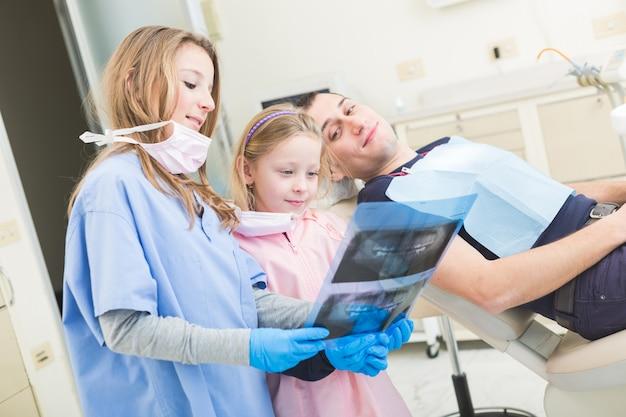 Dentistas pouco olhando para raio-x do paciente adulto