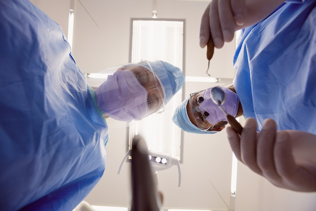 Dentistas segurando instrumentos dentários