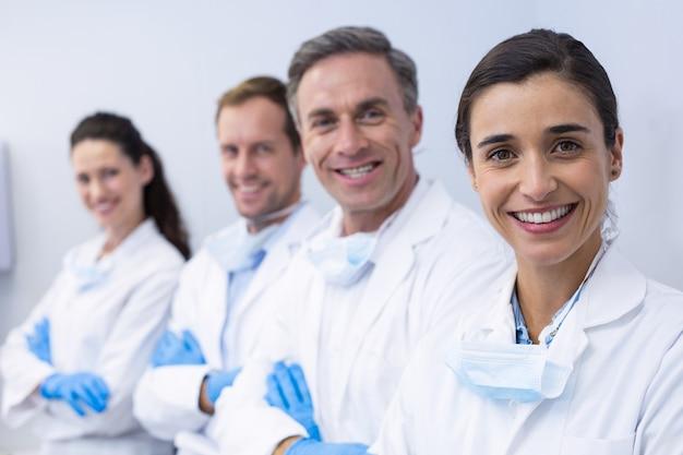 Dentistas sorridentes em pé com os braços cruzados