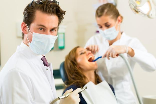 Dentistas, sua cirurgia, olhando para o espectador, em seu assistente, está dando tratamento a uma paciente do sexo feminino