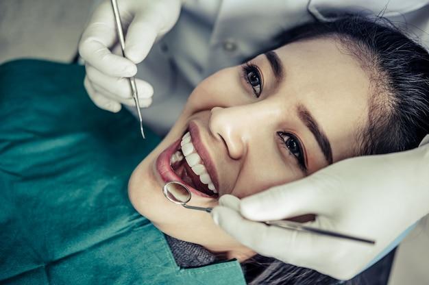Dentistas tratam os dentes dos pacientes.