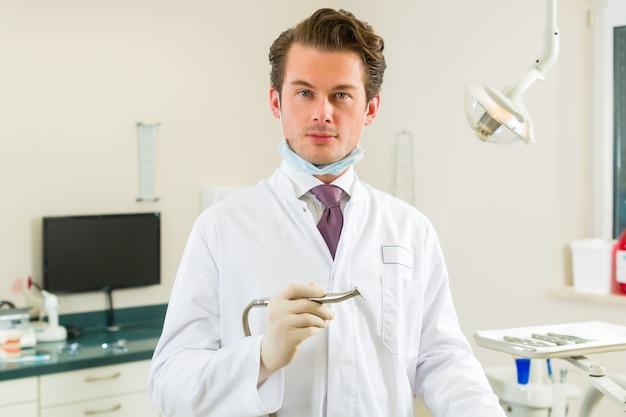 Dentistasesta cirurgia realiza uma broca e, olhando para o espectador, existem ferramentas para um dentista